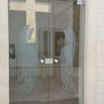 Sulla porta temperata con sabbiatura sono stati rappresentati due angeli che sorvegliano la porta d'ingresso di una cappella.